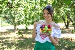 Schönes junges Mädchen, das eine Platte der Frucht und des Daumens oben angehoben hält Stockbilder