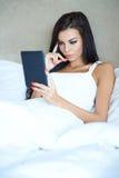 Schönes junges Mädchen, das eine Tablette im Bett liest Stockfotografie