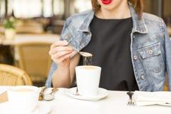 Schönes junges Mädchen, das in einem Café, Zucker in Kaffee hinzufügend sich entspannt lizenzfreie stockfotografie