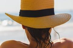 Schönes junges Mädchen, das einen gelben Strohhut am Strand trägt lizenzfreie stockbilder