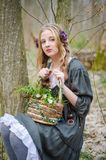 Schönes junges Mädchen, das einen Korb von Blumen hält stockfoto