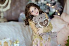 Schönes junges Mädchen, das einen Teddybären hält und im BAC lächelt stockbilder