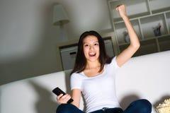Schönes junges Mädchen, das Fernsieht Lizenzfreie Stockfotografie