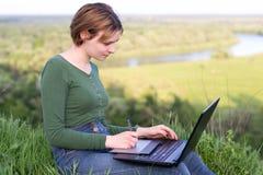 Schönes junges Mädchen, das ihre grafische Tablette sitzt im Gras nahe Fluss verwendet lizenzfreies stockbild