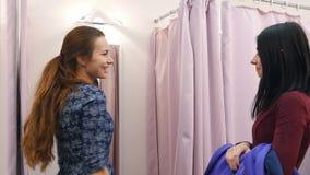 Schönes junges Mädchen, das ihrem Freund blaues Kleid in der Umkleidekabine, lächelnd zeigt stock footage
