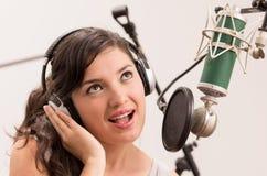 Schönes junges Mädchen, das im Musikstudio singt stockbilder