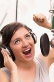 Schönes junges Mädchen, das im Musikstudio singt lizenzfreie stockfotos