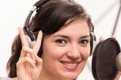 Schönes junges Mädchen, das im Musikstudio singt stockbild