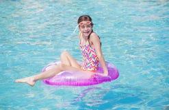 Schönes junges Mädchen, das im Pool in der Sommerzeit spielt stockfotos