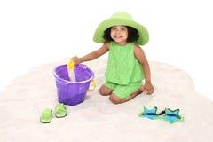 Schönes junges Mädchen, das im Sand-Spielen sitzt Lizenzfreies Stockbild