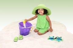 Schönes junges Mädchen, das im Sand-Spielen sitzt Lizenzfreies Stockfoto