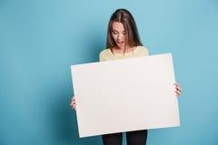 Schönes junges Mädchen, das leeres leeres Brett über blauem Hintergrund hält Lizenzfreie Stockfotografie