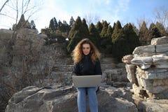 Schönes junges Mädchen, das mit einem Laptop im Park auf einem Hintergrund von Bergen sitzt Die Möglichkeiten sind im Internet en Stockfotografie