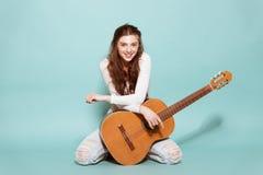 Schönes junges Mädchen, das mit Gitarre aufwirft Stockfoto