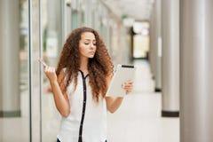 Schönes junges Mädchen, das mit Kreditkarte für zahlt Stockbild