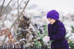 Schönes junges Mädchen, das mit Schnee im Park spielt lizenzfreie stockfotografie