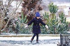 Schönes junges Mädchen, das mit Schnee im Park spielt stockfotos