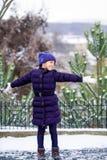 Schönes junges Mädchen, das mit Schnee im Park spielt lizenzfreie stockbilder