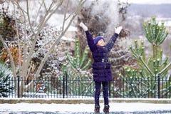 Schönes junges Mädchen, das mit Schnee im Park spielt lizenzfreies stockfoto