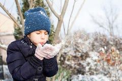 Schönes junges Mädchen, das mit Schnee im Park spielt stockfoto