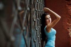 Schönes junges Mädchen, das nahen Zaun steht Lizenzfreies Stockbild