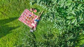 Schönes junges Mädchen, das sich draußen auf Gras, Sommerpicknick im Park habend, Vogelperspektive von oben entspannt stockbilder