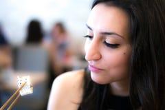 Schönes junges Mädchen, das Sushi schaut und isst lizenzfreies stockfoto