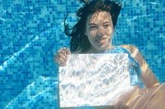 Schönes junges Mädchen, das weißes leeres Brett im Swimmingpool unter Wasser, Familienurlaub hält Lizenzfreies Stockbild