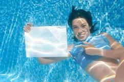 Schönes junges Mädchen, das weißes leeres Brett im Swimmingpool unter Wasser, Familienurlaub hält Stockbilder
