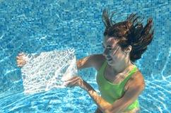 Schönes junges Mädchen, das weißes leeres Brett im Swimmingpool unter Wasser, Familienurlaub hält Stockfotos