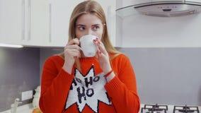 Schönes junges Mädchen in der roten Strickjacke trinkt Tee an der Küche stock footage