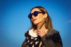 Schönes junges Mädchen in der Sonnenbrille gegen blauen Himmel Lizenzfreies Stockfoto