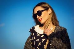 Schönes junges Mädchen in der Sonnenbrille gegen blauen Himmel Lizenzfreie Stockbilder