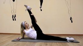 Schönes junges Mädchen in der Sportkleidung tut Übungen auf einem Erweiterungslügen stock footage