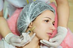 Schönes junges Mädchen des europäischen Auftrittes auf dem Verfahren des Einspritzens von Einspritzungen Stockfotografie