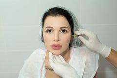 Schönes junges Mädchen des europäischen Auftrittes auf dem Verfahren des Einspritzens von Einspritzungen Stockfoto
