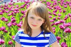 Schönes junges Mädchen des Porträts auf lila Tulpenhintergrund stockbild