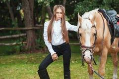 Schönes junges Mädchen des Porträts im weißen Hemd und in den schwarzen Hosen mit folgendem Pferd des langen Haares der Schö lizenzfreies stockbild