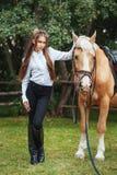 Schönes junges Mädchen des Porträts im weißen Hemd und in den schwarzen Hosen mit folgendem Pferd des langen Haares der Schö lizenzfreie stockfotografie