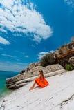 Schönes junges Mädchen durch das Meer Frau in einem roten Kleid auf dem Strand Küstenferien Felsiges Gelände stockfoto
