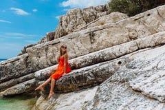 Schönes junges Mädchen durch das Meer Frau in einem roten Kleid auf dem Strand Küstenferien Felsiges Gelände lizenzfreie stockfotografie