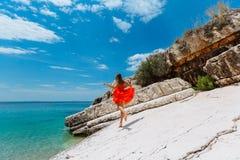Schönes junges Mädchen durch das Meer Frau in einem roten Kleid auf dem Strand Küstenferien Felsiges Gelände lizenzfreie stockfotos