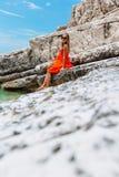 Schönes junges Mädchen durch das Meer Frau in einem roten Kleid auf dem Strand Küstenferien Felsiges Gelände lizenzfreies stockfoto