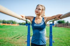 Schönes junges Mädchen in einem blauen Hemd und in den Gamaschen auf dem Stufenbarren, auf dem Sportplatz im Freien im Sommer Lizenzfreie Stockbilder