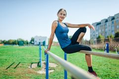 Schönes junges Mädchen in einem blauen Hemd und in Gamaschen, die auf dem Stufenbarren, auf dem Sportplatz im Freien im Sommer be Stockfotos