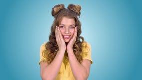 Schönes junges Mädchen in einem gelben Hemd zeigt Überraschung mit ihren Händen zu ihren Backen und zum Lächeln beim Untersuchung stock video