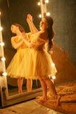 Schönes junges Mädchen in einem Goldabendkleid steht auf einer Pelzwolldecke nahe einem großen Spiegel in einem Rahmen mit Lichte stockfoto