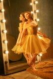 Schönes junges Mädchen in einem Goldabendkleid steht auf einer Pelzwolldecke nahe einem großen Spiegel in einem Rahmen mit Lichte lizenzfreies stockbild