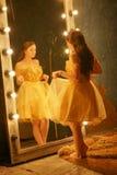 Schönes junges Mädchen in einem Goldabendkleid steht auf einer Pelzwolldecke nahe einem großen Spiegel in einem Rahmen mit Lichte lizenzfreie stockfotos