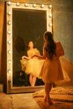 Schönes junges Mädchen in einem Goldabendkleid steht auf einer Pelzwolldecke nahe einem großen Spiegel in einem Rahmen mit Lichte stockfotos